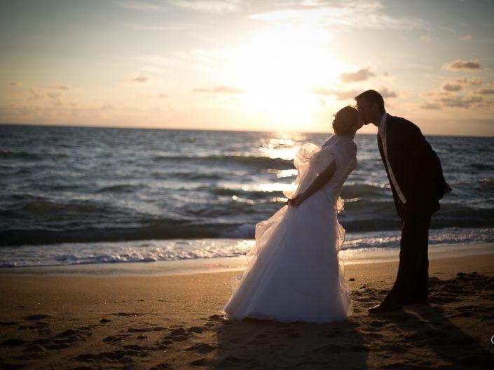 Les mariés s'embrassent au coucher du soleil